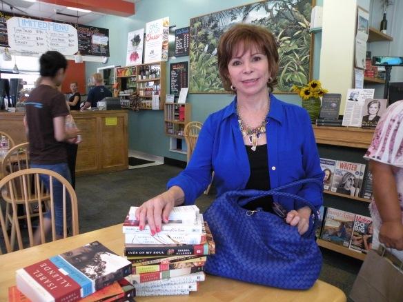 Isabel posa junto a algunos de sus libros y muestra su bolsa muy combinada. Foto María Antonieta Mejía